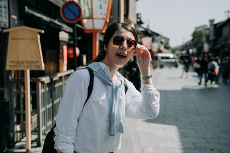 girl backpacker in sunglasses standing on traditional japanese town on Storm mountain street. asian woman tourist smiling self guided travel in kyoto japan. beautiful lady in white shirt tourism.