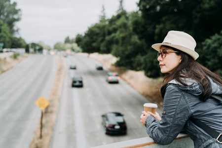 young girl tourist in straw hat standing on pedestrian overpass holding cup of coffee look down on the high way road with cars driving through on sunny day. female travel backpacker smiling outdoor.