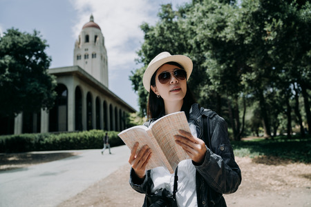 female asian student in sunglasses working and overseas study in university language learning in stanford. college girl abroad holding guided book and camera sightseeing at school in summer vacation. Фото со стока