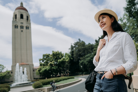 elegant student study abroad university in america stanford. young college girl smiling with tower church in background in summer. man riding bike on the road in ourdoor park with trees and plants. Standard-Bild