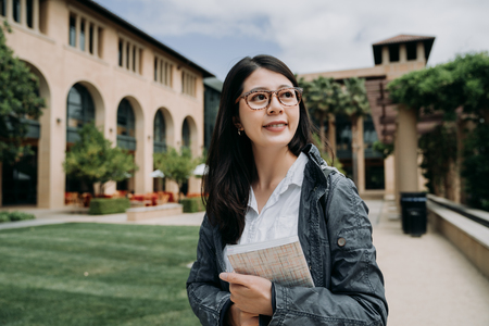 Attractive smiling charming asian young girl student with school book relaxing walking in university outdoor.