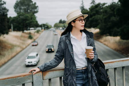 relaxing businesswoman stop walking standing relying on handrail while crossing walkway bridge. young girl holding cup of hot tea and backpack resting on pedestrian overpass outdoor wearing hat. 스톡 콘텐츠