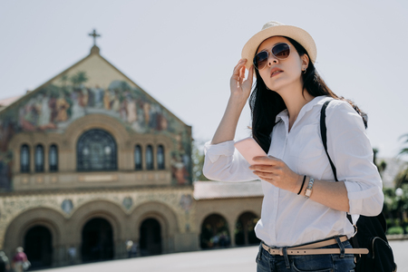 young asian girl tourist wearing sunglasses straw hat using mobile phone standing on front ground of church sightseeing in stanford. elegant traveler visiting while studying abroad in summer.