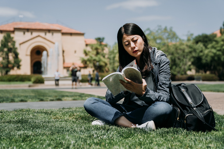 Portrait of happy charming asian woman reading a book outdoors in university.