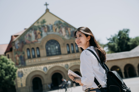 asian college girl carrying backpack and school book walking to church praying in the morning before go to class in university. Archivio Fotografico