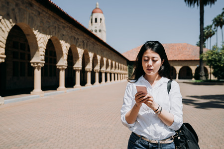 beautiful asian woman holding smartphone texting online message walking on brick ground with old architecture.