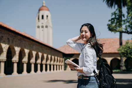 asian college girl standing outdoor going to class at school in summer tour program.  young woman freshman in new semester cheerful smile
