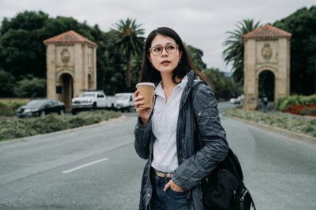young female professor going to work in morning to university. asian woman teaching chinese in school holding cup of coffee carry backpack walking on the road.