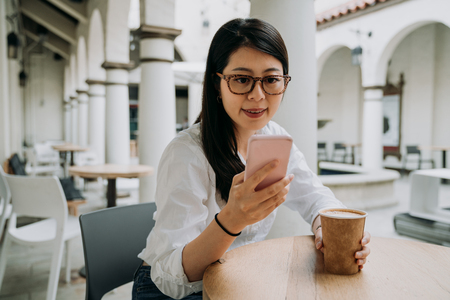 smiling asian woman in glasses texting message chatting online on smartphone. young businesswoman holding coffee cup at the table outdoors cafe. female worker relaxing in break time in afternoon. 免版税图像