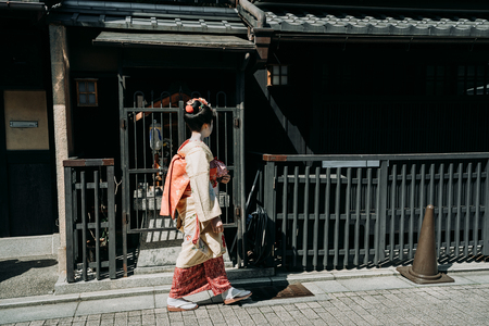 side view of local japanese female people in traditional kimono cloth walking on road. full length of young maiko geisha going to work ready makeup done. old iron house with handrails fence in town. Imagens