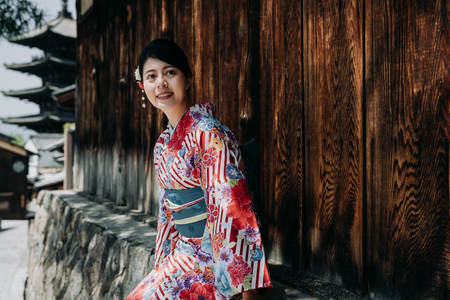 elegant asian woman wearing colorful kimono dress sitting under tree shadow relying on wooden wall with yasaka pagoda in background. young girl smiling relaxing on street wear traditional cloth.