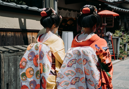 back view of two maiko geisha walking on a street of Gion in Kyoto Japan. japanese girls wearing traditional cloth dress kimono with amazing makeup and hair in old town on sunny day.