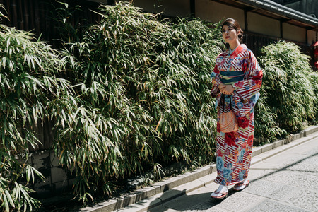 full length of young local girl in kimono dress walking along the bamboo garden plants by old wooden historical house. elegant woman in colorful traditional cloth under sunshine going to visit friend Imagens