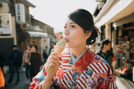 japanese young teenage girl in flower kimono dress join having fun in summer festival join temple fair. happy woman in traditional cloth eating matcha ice cream kyoto japan in hot teeming street Foto de archivo