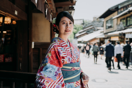 gorgeous japanese woman walking out from restaurant after having lunch in afternoon. young local girl cheerful standing on kiyomizu zaka street with many tourists walk by. beautiful lady in kimono.