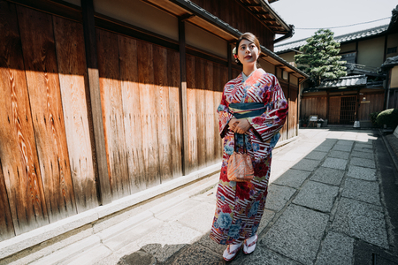 full length of young japanese woman in traditional cloth going to visit family in old town in new year walking along the wooden wall on stone road in ishibe alley. local girl in kimono enjoy sunlight