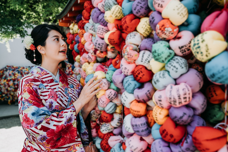 young local teenager girl religion praying gracing in kongoji temple kyoto japan. japanese woman in kimono dress hanging on colorful wish ball on wall with hopes. lady in traditional cloth