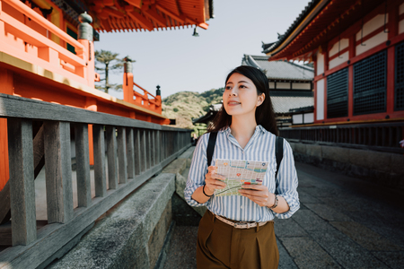 young girl traveler smiling visiting in japanese red wooden shrine in passage way.