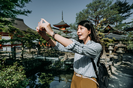 girl tourist holding cellphone camera app taking picture of beautiful scenery in japanese garden near shrine. Stock Photo