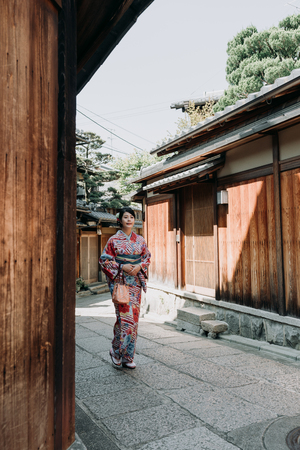 full length of female local people walking on passageway surrounding by wooden house in ishibe alley kyoto japan wearing colorful kimono dress. beautiful japanese lady in traditional cloth relax.