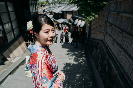 young japanese woman in floral traditional dress in old town on sunny day. beautiful lady in colorful kimono visiting sannen zaka street kyoto japan. charming girl smiling looking aside bamboo wall