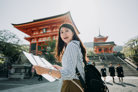 Happy female asian tourist sightseeing kyoto city famous tourism attraction with map.