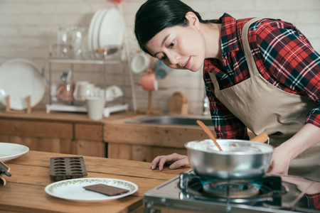 young chinese girl in pinafore turning on burner to cook meal. woman in apron open stove on fire to melt chocolate handmade dessert for valentine day gift for husband. elegant female prepared present