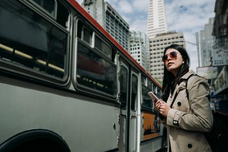 szczęśliwa kobieta turysta stojący na ulicy w pobliżu przystanku autobusowego czeka wyszukiwanie harmonogramu na telefon. młodzi ludzie dojeżdżają do technologii. lekki pociąg kolejowy blisko jazdy przechodzą na drodze w ruchliwym mieście z błękitnym niebem. Zdjęcie Seryjne