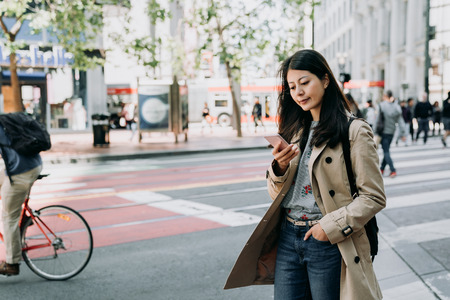 elegant asian office lady standing in city street using cellphone replying texting message. many people walking on zebra cross to protect pedestrian safety. young woman smiling with bike riding pass Banque d'images