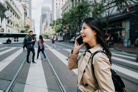 happy asian woman worker talking on cellphone having fun chatting with friends laughing. young office lady crossing zebra road light railway in city san francisco. busy business area public commute