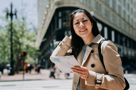 female college student face camera smiling while sightseeing city san francisco with paper map in hand. confident young girl backpacker self guided trip usa summer vacation. flatiron building in back