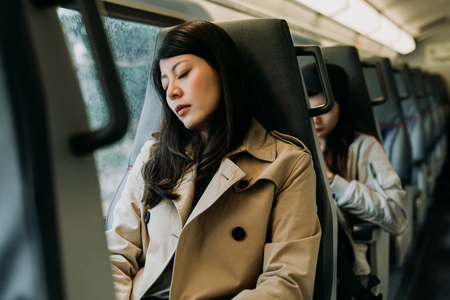 Traveler woman sleeping in a train travel beside the window. tired chinese lady worker in smart casual commute to work take a nap. young girl sitting on seat on subway fell asleep in quiet place.