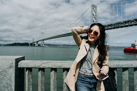 travel asian woman charming smiling relying on handrail holding smart phone. boat sail on water blue clear ocean in background under oakland bay bridge san francisco on sunny day wearing sunglasses.