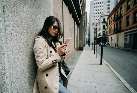 young elegant office lady relying on wall standing in quiet street in busy city urban in san francisco usa. asian woman using mobile phone chatting online waiting near building in cloudy day. 版權商用圖片