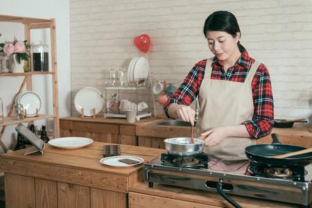 Kochen glückliche Frau trägt Schürze in Holzküche mit Topf rühren schmelzender Schokolade, um süßes Dessert für den Valentinstag zuzubereiten. junge schöne Freundin handgemachter Kakao mit Löffel kochen auf dem Herd.