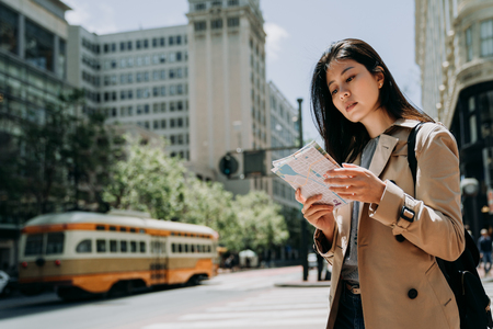 Young asian female tourist checking out the sights while reading paper map. gorgeous woman holding guide information while touring abroad. stylish chinese girl backpacker standing in urban in summer