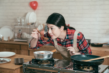 smiling young chinese girl prepared dessert gift on valentine day for husband. woman holding wooden spoon smelling melting chocolate with high temperature in pot on stove ready to make sweet cocoa