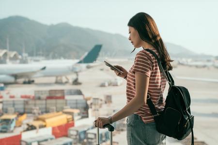 zijaanzicht van mooie reisdame met rugzak en bagagekoffer die naar de vertreklounge in de hal loopt. toeristische vrouw die in de buurt van het raam staat met behulp van mobiele telefoon die online vliegtuigen aan het chatten is op de startbaan.