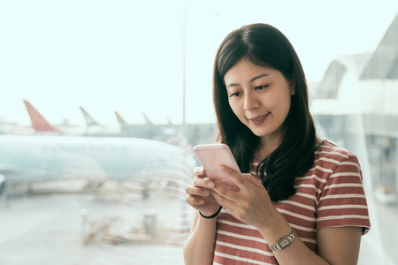 hong kong airport phone travel Asian exchange college student using mobile smartphone in business class lounge waiting for plane flight texting sms message. Technology and travel people VIP lifestyle Stock Photo