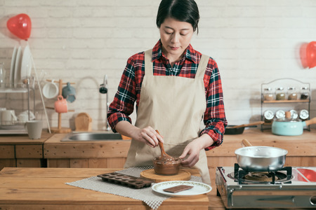 elegant asian woman standing in modern wooden kitchen holding spoon stir melting chocolate in glass bowl. beautiful lady prepared cooking handmade sweet dessert for valentine day with balloon in back