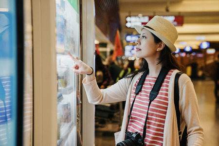 asian travel woman photographer using modern vending machine in airport while waiting for plane flight in departure gate. young girl right hand finger pointing choosing snack drinks to buy. Stockfoto
