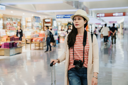 young girl pass the e gate walk in lobby airport shopping tax free area. lady passenger going to departure gate with luggage. beautiful woman in hat camera relax indoor through specialty local shop