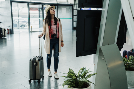 Happy young woman arrived airport going departure start trip. girl walking standing at sign timetable schedule of flight with luggage. lady in casual wear looking at monitor information indoors. Reklamní fotografie