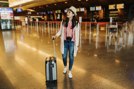 full length of serious young chinese woman is looking for right direction on information board at airport. asian girl traveler standing near suitcase in lobby with check in counter in background. Reklamní fotografie
