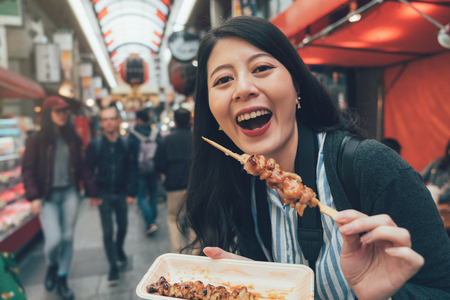 local food festival japanese market concept. female traveler visit kuromon ichiba osaka trying delicious street food of barbecue chicken. happy lady showing tasty snack in teeming place.