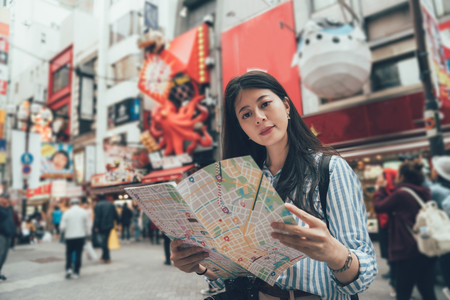vintage style of young asian tourist self guided trip in osaka japan on holidays. elegant woman traveler standing in dotonbori street teeming popular area hold paper map discover tourism attraction