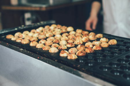 Process of cooking Takoyaki on hot pan famous street food osaka japan. unrecognized chief in white apron waiting for local octopus ball ready. delicious tasty snack in japanese style.