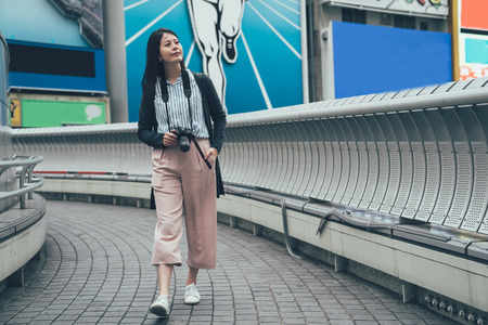 full length of young japanese lady visiting osaka city japan on weekend. woman walking on dotonbori bridge carrying professional camera looking aside smiling. beautiful tourist outdoor sightseeing.