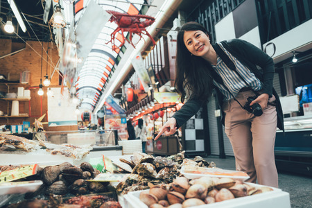vintage photo of young asian woman with camera cheerful smiling pointing showing stand selling fresh seafood at Kuromon Ichiba in Osaka Japan spacious market with vendors selling street food.