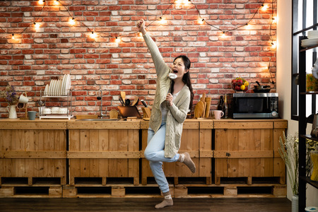Dancing and singing while cooking in kitchen fun spirited joyful attitude chores. young asian woman raising hands smiling cheerful with one leg left from wooden floor. joyful happy music lady singer. Stock Photo